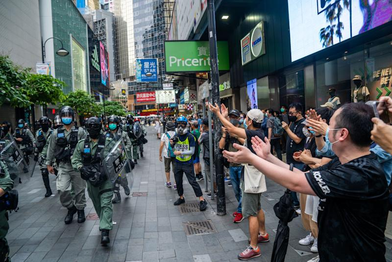 Protesters seen sarcastically clapping to the police as they retreat from the front line. Source: Getty