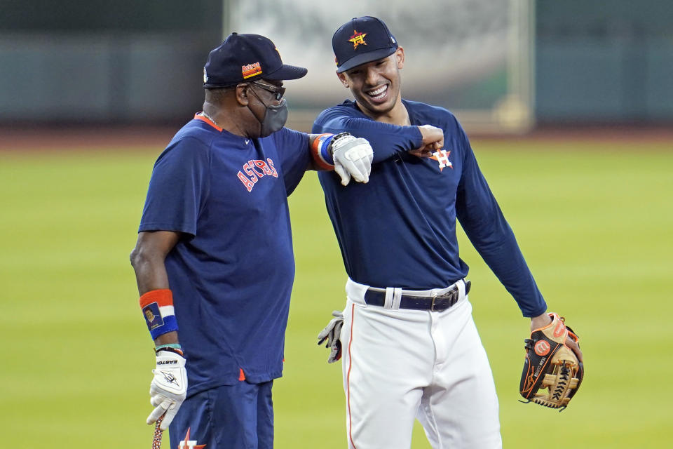 Houston Astros' Carlos Correa, right, bumps elbows with manager Dusty Baker during a baseball practice at Minute Maid Park, Saturday, July 4, 2020, in Houston. (AP Photo/David J. Phillip)