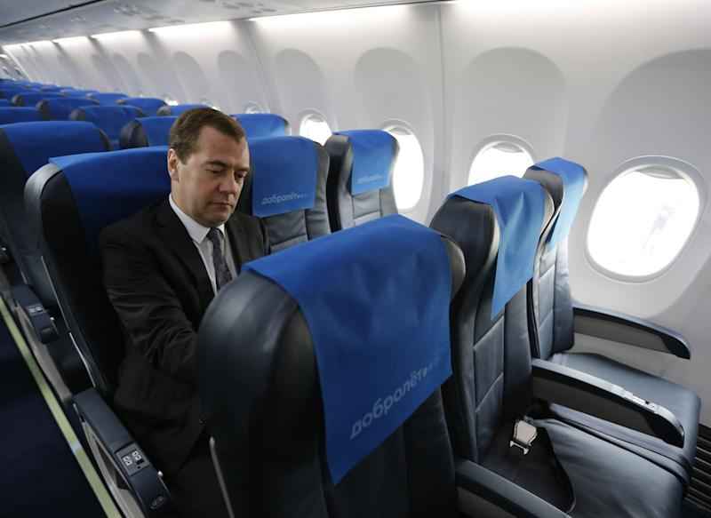 A picture taken at Moscow's Sheremetyevo airport on June 10, 2014, shows Russia's Prime Minister Dmitry Medvedev inspecting a passenger jet of Aeroflot's new budget airline subsidiary, Dobrolet