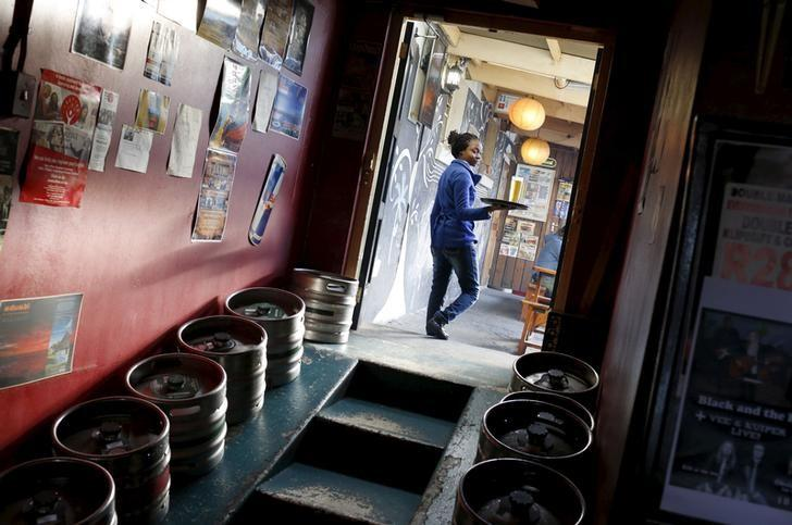 A woman carries beer produced by brewing company SAB Miller past kegs at a bar in Cape Town