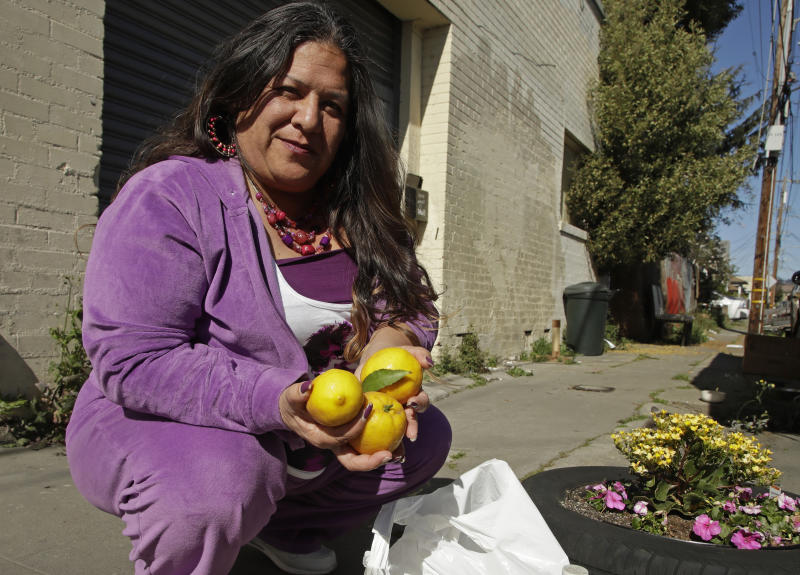 Needa Bee, who lives in a camper in Oakland with her teenage daughter, holds lemons, Thursday, April 2, 2020, in Oakland, Calif.  Bee is the founder of a grassroots collective that administers to roughly 40 Oakland homeless encampments. They've been asking for donations of lemons and vinegar to sanitize hands since bleach and Lysol are so hard to get, distributing raw garlic for an immune boost, and collecting aloe plants to make hand sanitizer.   (AP Photo/Ben Margot)