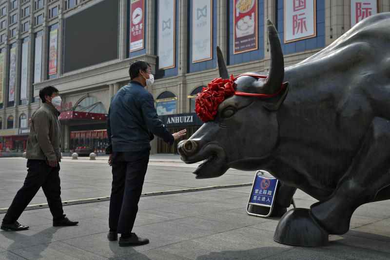 A man wearing a protective face mask touches the investment icon bull statue on display outside a retail and wholesale clothing mall which remain closed following the new coronavirus outbreak in Beijing, Monday, March 30, 2020. Asian shares started the week with fresh losses as countries reported surging numbers of infections from the coronavirus that has prompted shutdowns of travel and business in many parts of the world. (AP Photo/Andy Wong)