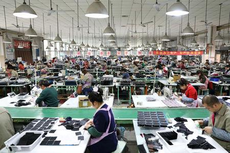 Employees work on the production line of a factory manufacturing fashion accessories in Sihong