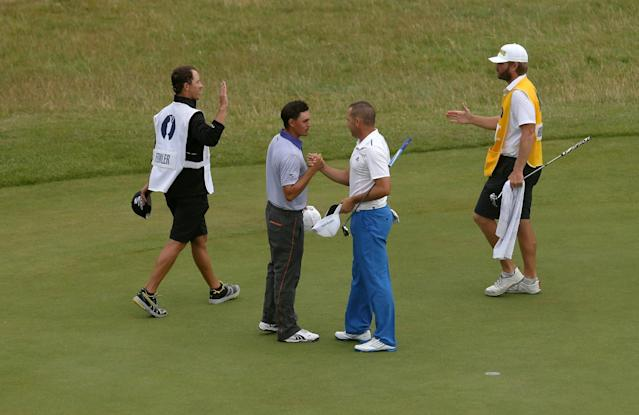 Rickie Fowler of the US, second left, shakes hands with Sergio Garcia of Spain on the 18th green at the end of their match on the third day of the British Open Golf championship at the Royal Liverpool golf club, Hoylake, England, Saturday July 19, 2014. (AP Photo/Peter Morrison)