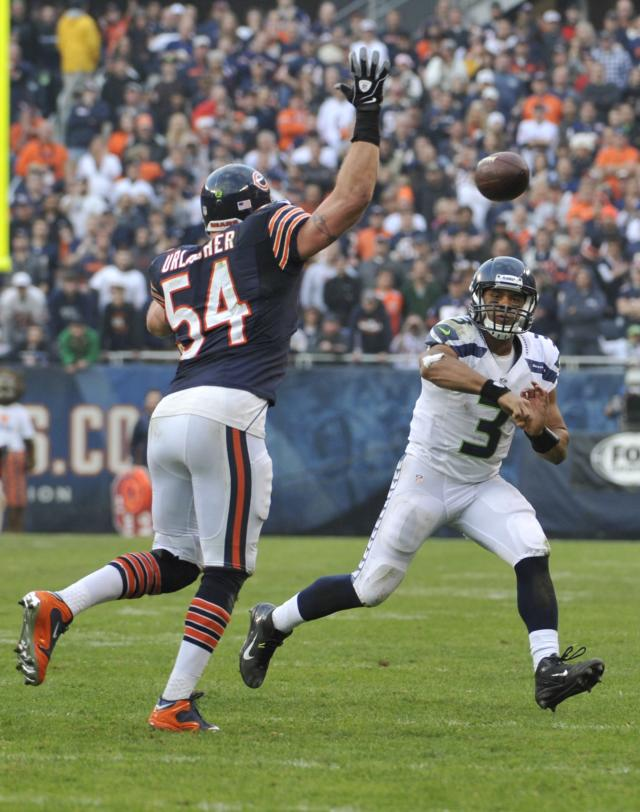 CHICAGO, IL - DECEMBER 02: Russell Wilson #3 of the Seattle Seahawks passes the ball as he's pressured by Brian Urlacher #54 of the Chicago Bearson December 2, 2012 at Soldier Field in Chicago, Illinois.The Seattle Seahawks defeated the Chicago Bears 23-17 in overtime. (Photo by David Banks/Getty Images)