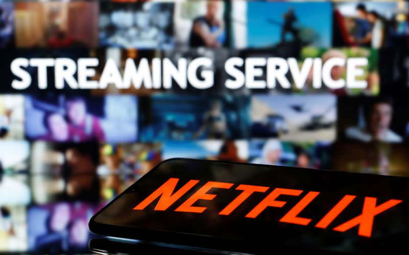 """A smartphone with the Netflix logo lies in front of displayed """"Streaming service"""" words in this illustration"""