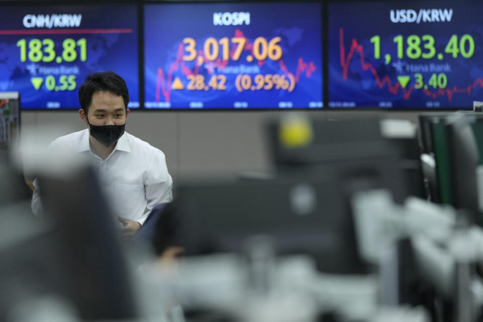 A currency trader passes by screens showing the Korea Composite Stock Price Index (KOSPI), center, and the foreign exchange rate between U.S. dollar and South Korean won, right, at the foreign exchange dealing room of the KEB Hana Bank headquarters in Seoul, South Korea, Friday, Oct. 15, 2021. Asian shares were higher Friday after technology companies powered the biggest gain on Wall Street since March. (AP Photo/Ahn Young-joon)