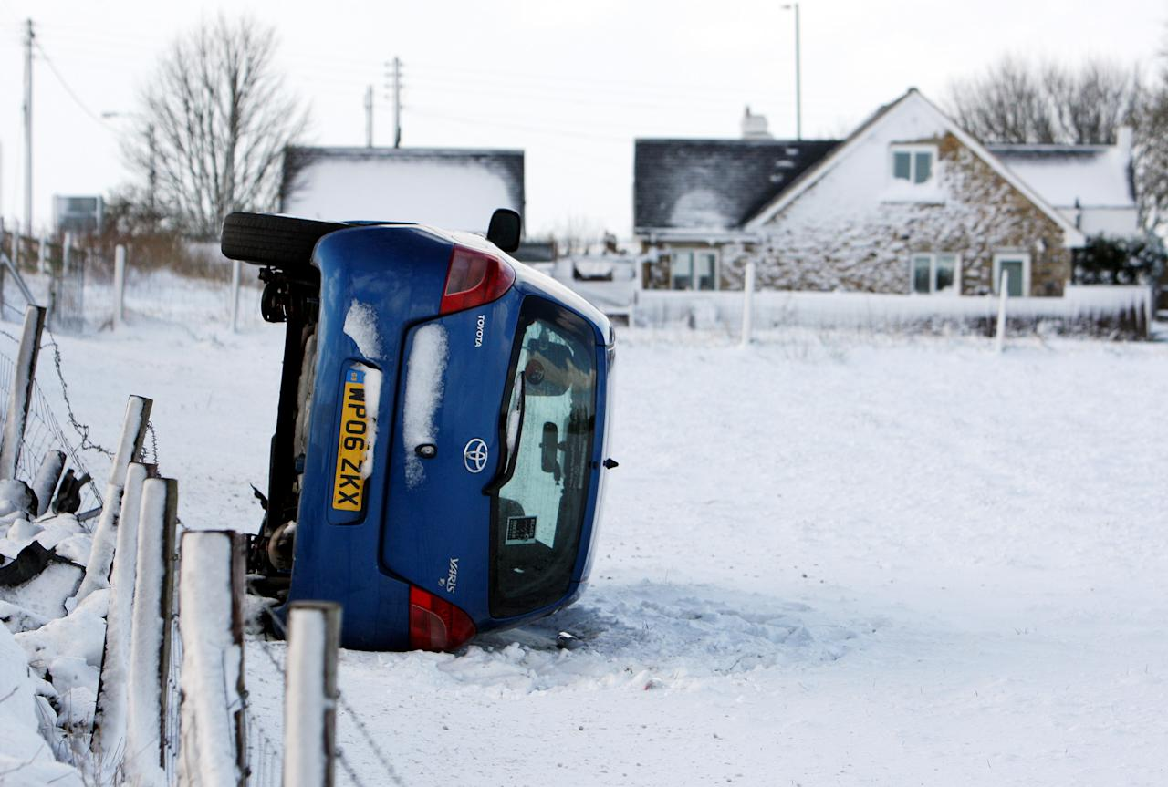 A overturned car, is seen after it left the road and came to rest in a snowy field at Anfield Plain, England, Wednesday, April 4, 2012. Parts of Scotland and northern England have received 20 centimeters (8 inches) of snow, and 10,000 homes are without power in northeast England after wind brought down power cables. (AP Photo/Scott Heppell)
