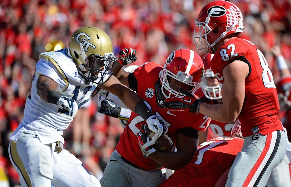Georgia running back Nick Chubb (27) gets past Georgia Tech defensive back Demond Smith (12) for a touchdown with blocking from teammate Michael Bennett (82) during the first half of an NCAA college football game Saturday, Nov. 29, 2014, in Athens, Ga. (AP Photo/David Tulis)