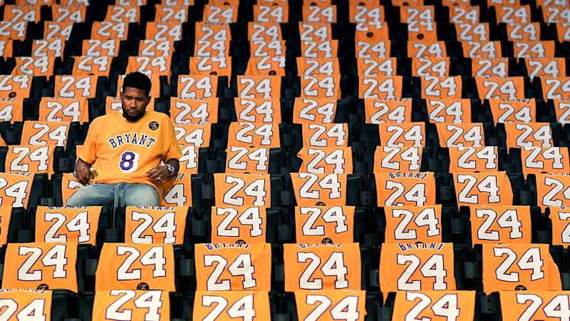 Usher, pictured here sitting alone in the stands at Staples Centre before his performance.