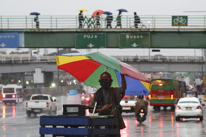 A vendor pushes his cart under an umbrella to shield him from rain from Typhoon Vamco in Quezon city, Philippines on Wednesday, Nov. 11, 2020. Typhoon Vamco blew closer Wednesday to a northeastern Philippine region still struggling to recover from a powerful storm that left a trail of death and destruction just over a week ago, officials said, adding that thousands of villagers were being evacuated again to safety. (AP Photo/Aaron Favila)
