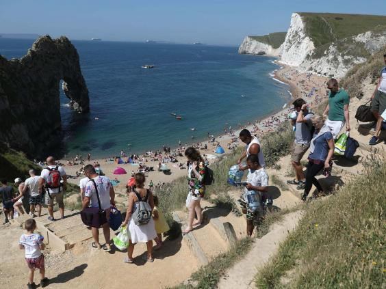 People make their way down to the sea Durdle Door as the public have been allowed to go to beaches (Andrew Matthews/PA Wire)