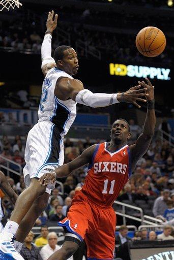 Orlando Magic center Dwight Howard, left, disrupts a shot by Philadelphia 76ers guard Jrue Holiday during the first half of an NBA basketball game in Orlando, Fla., Wednesday, Feb. 15, 2012. (AP Photo/Phelan M. Ebenhack)