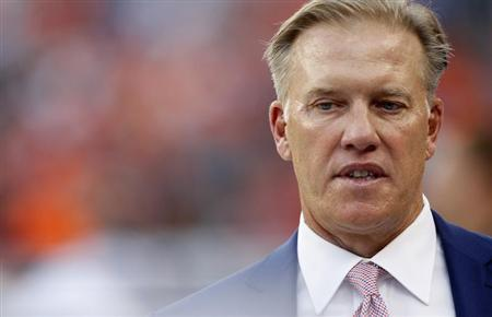 Denver Broncos Executive Vice President of Football Operations Elway walks on field before NFL football game against Baltimore Ravens in Denver