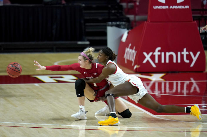 Maryland guard Diamond Miller, right, and Wisconsin guard Estella Moschkau compete for a loose ball during the first half of an NCAA college basketball game, Thursday, Feb. 4, 2021, in College Park, Md. (AP Photo/Julio Cortez)