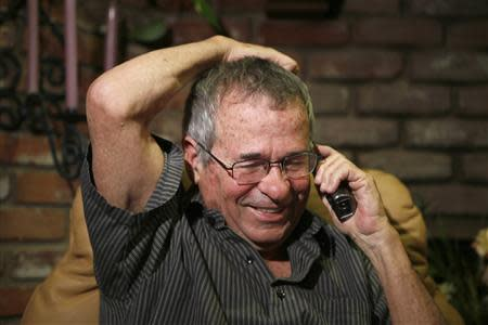 University of Southern California professor Warshel talks on the phone with Israeli President Peres after hearing he won the Nobel chemistry prize in Los Angeles, California