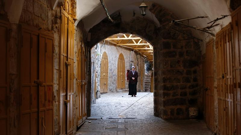 A Palestinian woman walks past shuttered shops in one of the ancient bazaars of the West Bank city of Hebron (AFP Photo/HAZEM BADER)