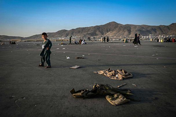 PHOTO: An child walks near abandoned Afghan military uniforms as he waits with elders to leave the Kabul airport in Kabul, Afghanistan, Aug. 16, 2021. (Wakil Kohsar/AFP via Getty Images)