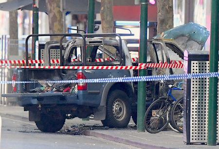 A burnt out vehicle is surrounded by police tape on Bourke Street in central Melbourne
