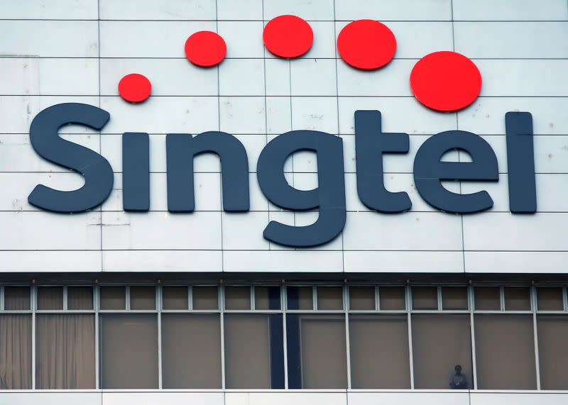 FILE PHOTO A man looks out of the window under a Singtel signage at their head office in Singapore