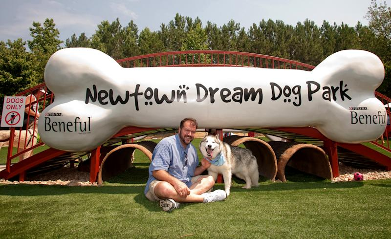 This June 15, 2011 photo released by Beneful shows Grand Prize Winner of the 2010 Beneful Dream Dog Park Contest, Pat McNeely and Koda, at the unveiling of their Dream Dog Park in Johns Creek, Ga . The dog park offers water splash pads, a 3-D dog bone bridge and crawl tunnels. (AP Photo/Beneful)
