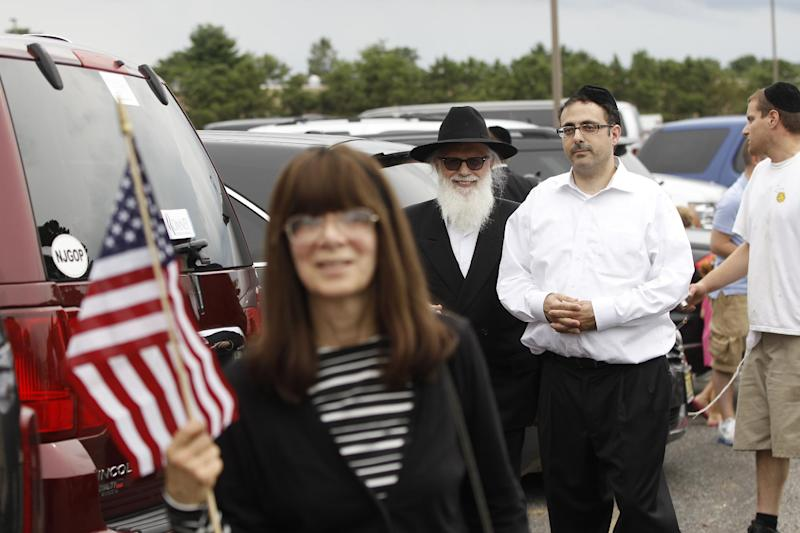 Members of a Jewish wedding party react as the motorcade of Republican presidential candidate and former Massachusetts Gov. Mitt Romney drives past for a campaign fundraising event in Lakewood, N.J., Wednesday, Aug. 8, 2012. (AP Photo/Charles Dharapak)