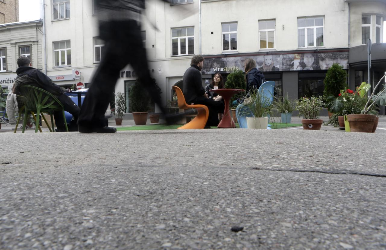 A man walks past people participating in a PARK(ing) Day event in Riga, September 20, 2013. The event aims to transform metered parking spaces into temporary public places to call attention to the need for more urban open spaces and discuss the creation and allocation of public spaces, according to organizers. REUTERS/Ints Kalnins (LATVIA - Tags: SOCIETY)