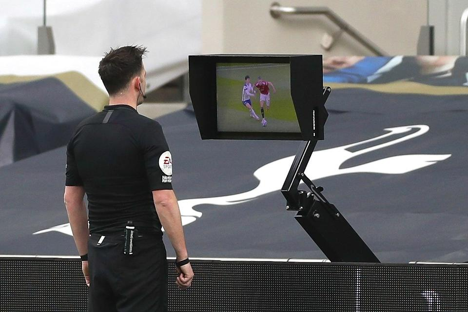 <p>Chris Kavanagh looks at the incident on his pitchside monitor</p> (Getty)