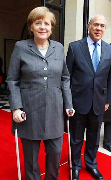 Head of the Organization for Economic Co-operation and Development (OECD) Angel Gurria, right, poses for photographers with Germany's Chancellor Angela Merkel prior to their meeting at the OECD headquarters in Paris, Wednesday, Feb. 19, 2014. Merkel uses crutches after a skiing accident. (AP Photo/Michel Spingler)