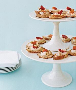 "<b>Cake Stand as Appetizer Server</b><p class=""caption"">To cut down on waiting time  for hors d'oeuvres, stack a small cake stand on top of a larger one to  increase your surface area for canapés or crudités and free up precious  table space.</p>"