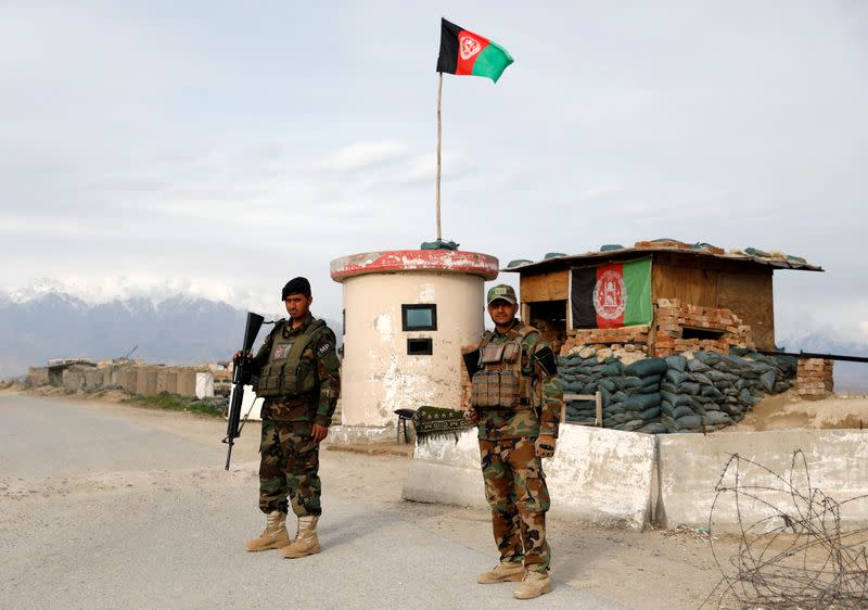 Afghan National Army (ANA) soldiers stand guard at a checkpoint outside Bagram prison, north of Kabul