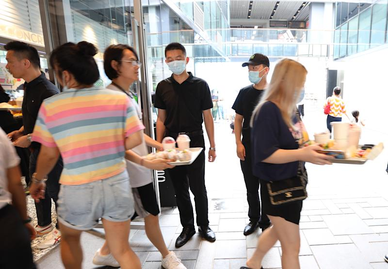 BEIJING, CHINA - AUGUST 13: Customers wearing face masks pick up their orders at a Shake Shack restaurant at Sanitun on August 13, 2020 in Beijing, China. Shake Shack opened its first restaurant in Beijing on Wednesday. (Photo by VCG/VCG via Getty Images)