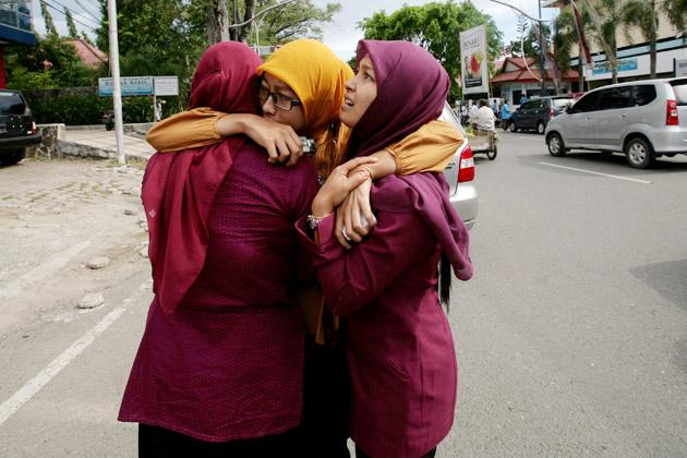 Acehnese women hug each other and pray shortly after a powerfull earthquake hit the western coast of Sumatera in Banda Aceh on April 11, 2012.  A massive earthquake struck off Indonesia's Sumatra island, US and Indonesian monitors reported, prompting an Indian Ocean-wide tsunami alert.         AFP PHOTO / CHAIDEER MAHYUDDIN