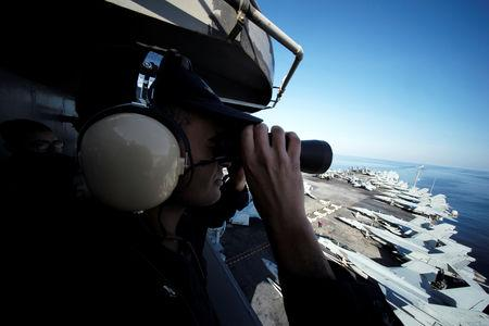 A U.S sailor keeps watch from the captain's bridge onboard the USS John C. Stennis as it makes its way to the Gulf through the Strait of Hormuz