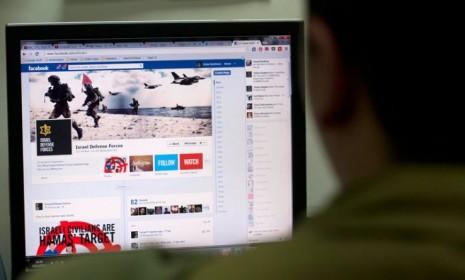 An Israeli solder looks at the Facebook page of the Israeli Defense Forces on Nov. 15: Social media has become a virtual battleground in Israel's Hamas offensive.