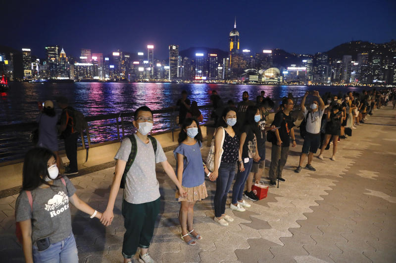 """Demonstrators link hands as they gather at the Tsim Sha Tsui waterfront in Hong Kong, Friday, Aug. 23, 2019. Demonstrators were planning to form 40 kilometers (25 miles) of human chains Friday night to show their resolve. They said the """"Hong Kong Way"""" was inspired by the """"Baltic Way,"""" when people in the Baltic states joined hands 30 years ago in a protest against Soviet control. (AP Photo/Vincent Yu)"""