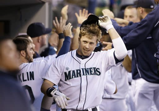 Seattle Mariners' Justin Smoak smiles in the dugout after hitting a three-run home run against the Los Angeles Angels in the sixth inning of a baseball game Saturday, July 13, 2013, in Seattle. (AP Photo/Elaine Thompson)