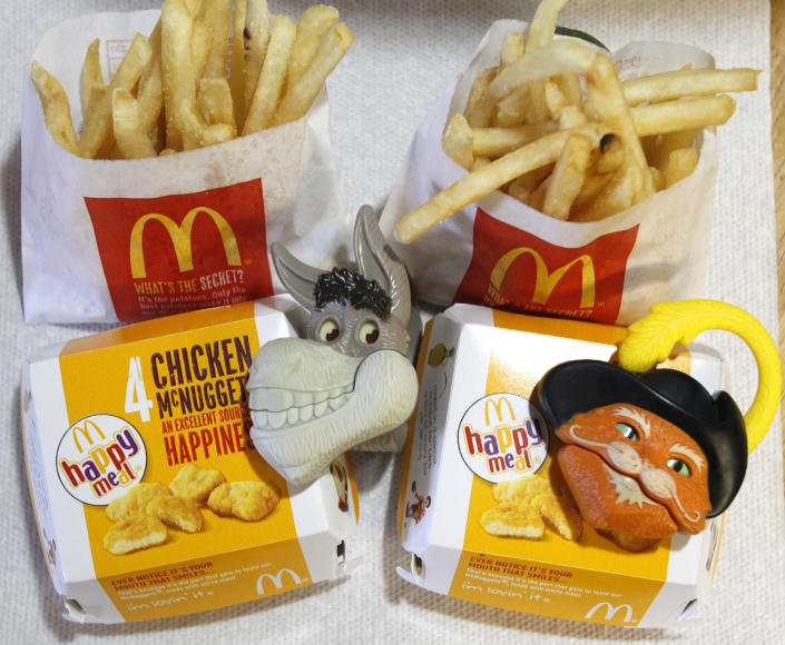 """Two McDonald's Happy Meal with toy watches fashioned after the characters Donkey and Puss in Boots from the movie """"Shrek Forever After"""" are pictured in Los Angeles June 22, 2010. A U.S. consumer group wants McDonald's Corp to stop using Happy Meal toys to lure children into its restaurants and has threatened to sue if the world's biggest hamburger chain does not comply within 30 days. REUTERS/Mario Anzuoni (UNITED STATES - Tags: FOOD CRIME LAW BUSINESS)"""