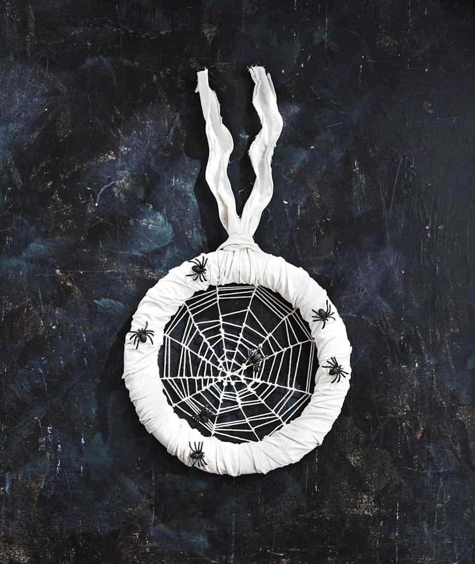 "<p>This wreath will definitely give your guests the creepy crawlies. Enter if you dare!</p><p><strong>Make the Spider Wreath: </strong>Tie six pieces of white string across a 14-inch foam wreath form, making sure to loop each one at the midway point of the first piece attached to create a central point. (This is the base of the web and should have 12 ""spokes."") Tie a long piece of string to the center point; weave and loop from the center out to create the web. If you run out of string, tie another piece to the end and continue weaving. When you reach the wreath form, tie off at your ending point. Move the twine up and down to create uneven gaps in the web. Wrap the wreath form with white burlap ribbon and attach faux spiders with hot-glue. Loop a piece of white burlap ribbon around the form to hang.</p><p><a class=""link rapid-noclick-resp"" href=""https://www.amazon.com/14-Smooth-Foam-Ruled-Wreath/dp/B01MR48RMZ/?tag=syn-yahoo-20&ascsubtag=%5Bartid%7C10050.g.22350299%5Bsrc%7Cyahoo-us"" rel=""nofollow noopener"" target=""_blank"" data-ylk=""slk:SHOP WREATH FORMS"">SHOP WREATH FORMS</a></p>"