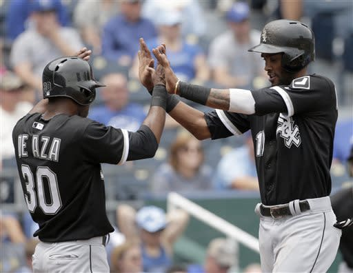 Chicago White Sox's Alexei Ramirez and Alejandro De Aza (30) celebrate after they scored on a single by Adam Dunn during the first inning of a baseball game against the Kansas City Royals, Sunday, June 23, 2013, in Kansas City, Mo. (AP Photo/Charlie Riedel)