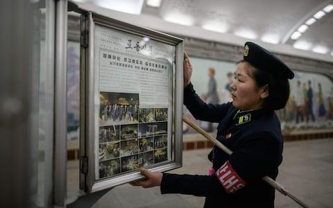 A conductor changes the Rodong Sinmun newspaper showing images of North Korean leader Kim Jong Un in Singapore on a Pyongyang subway platform - Credit: Ed Jones/AFP