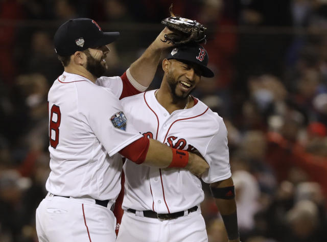 Boston Red Sox's Mitch Moreland, left, celebrates with Eduardo Nunez after Game 1 of the World Series baseball game Tuesday, Oct. 23, 2018, in Boston. The Red Sox won 8-4 to take a 1-0 lead in the series. (AP Photo/David J. Phillip)