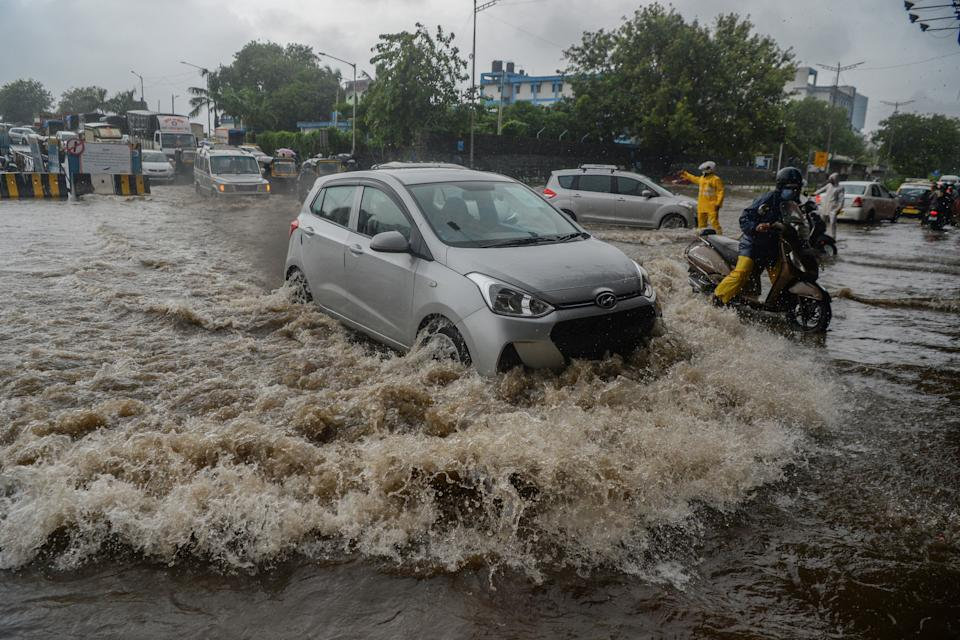 Motorists drive through a flooded road during a heavy monsoon rain in Mumbai on August 4, 2020. (Photo by INDRANIL MUKHERJEE/AFP via Getty Images)