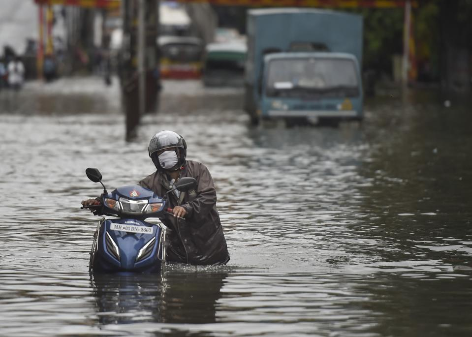 Mumbai: A commuter wades through a waterlogged street after heavy monsoon rain, at Sion in Mumbai, Wednesday, Sept. 23, 2020. (PTI Photo/Kunal Patil)(PTI23-09-2020_000075A)