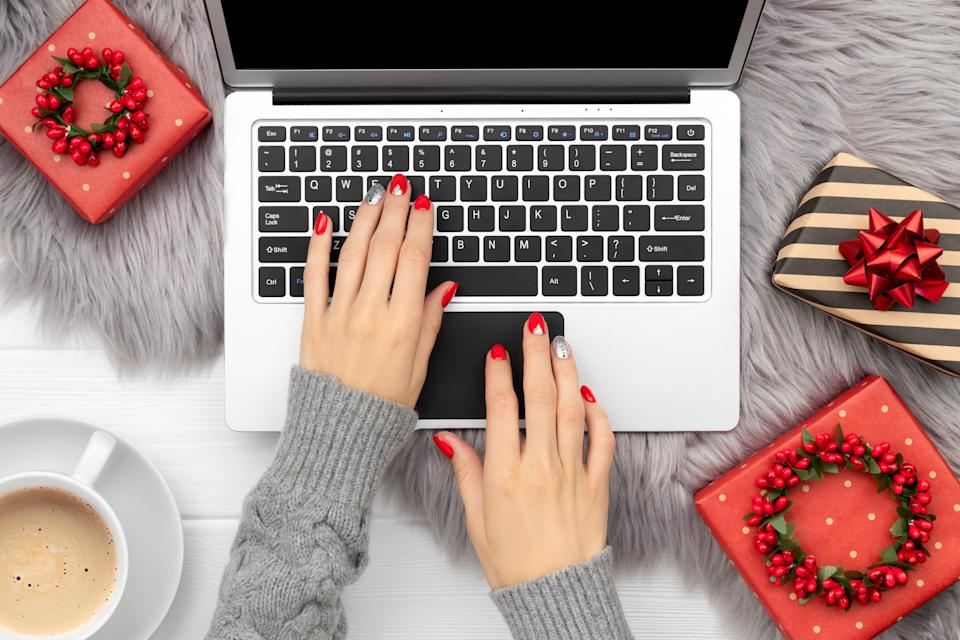 Womans hands with trendy red manicure typing on the keyboard. Christmas new year fashion clothes and accessories. Online shopping sale concept