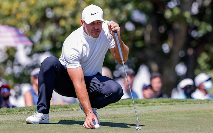 Brooks Koepka of the USA lines up his shot on the fifth hole during the third round of the 2021 TOUR Championship golf tournament - Shutterstock