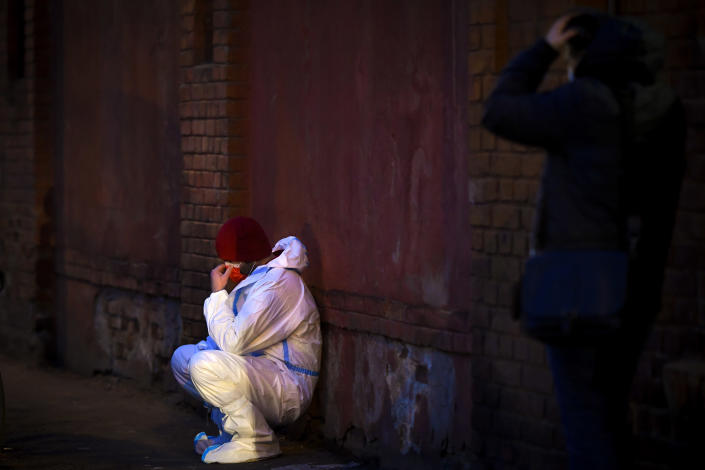An emergency paramedic leans against a wall outside the Matei Bals hospital compound in Bucharest, Romania, Friday, Jan. 29, 2021. A fire early Friday at a key hospital in Bucharest that also treats COVID-19 patients killed four people, authorities said. (AP Photo/Andreea Alexandru)