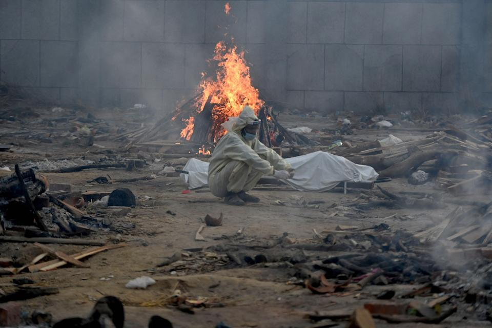 <p>A man sits next to the body of a victim who died of the Covid-19 coronavirus besides the burning pyre of another victim at a cremation ground in New Delhi on April 26, 2021.</p> (Photo by MONEY SHARMA/AFP via Getty Images)