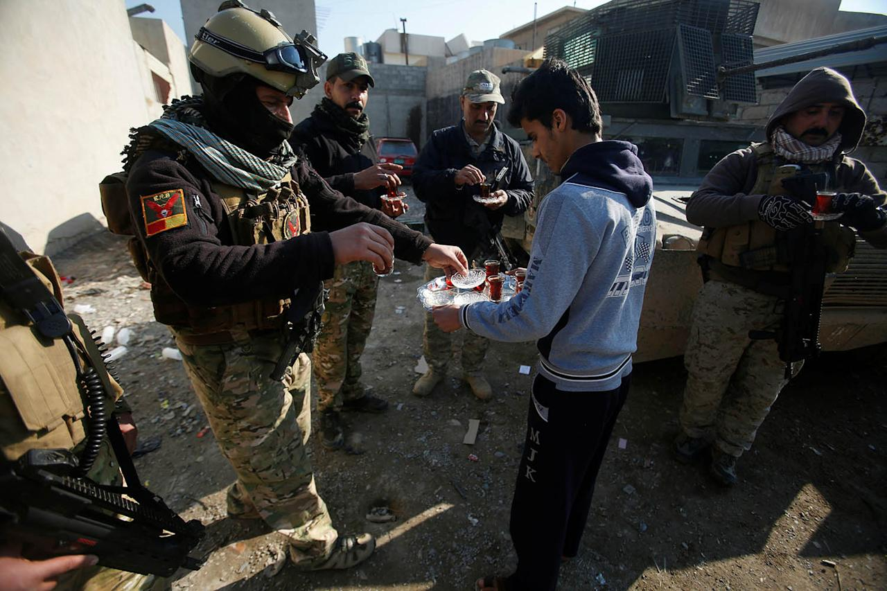 <p>A civilian hands out tea to members of the Iraqi rapid response forces during a battle with the Islamic State militants in the Mithaq district of eastern Mosul, Iraq, Jan. 5, 2017. (Photo: Khalid al Mousily/Reuters) </p>