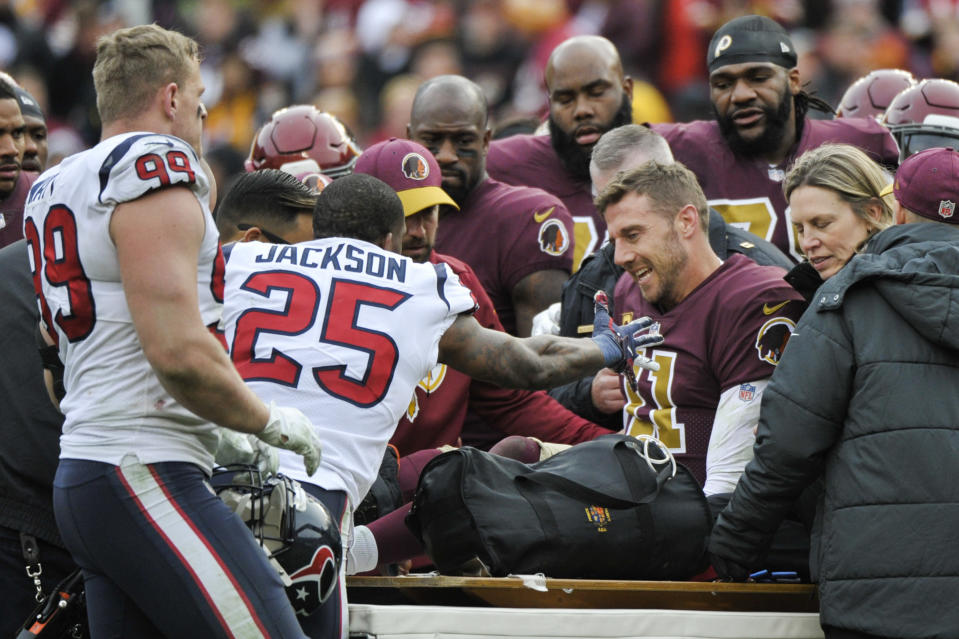 """Texans safety <a class=""""link rapid-noclick-resp"""" href=""""/nfl/players/23995/"""" data-ylk=""""slk:Kareem Jackson"""">Kareem Jackson</a> (25) reaches out in support of Redskins quarterback Alex Smith (11) as he leaves the field after a devastating injury on Nov. 18, 2018. (AP Photo/Mark Tenally)"""
